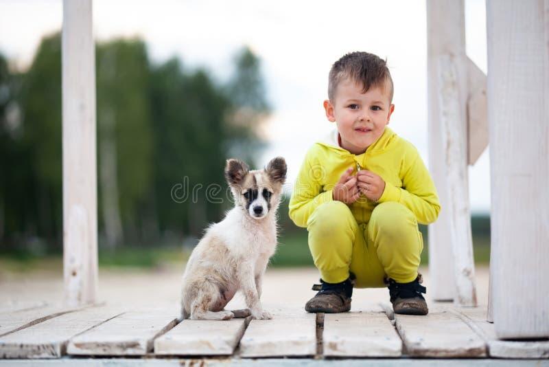 有他的小狗的逗人喜爱的小男孩 r 免版税库存图片