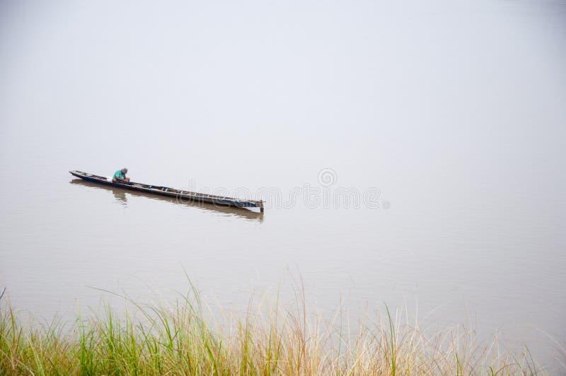 有他的小船的渔夫在有绿草的湄公河作为前景和空白 库存照片