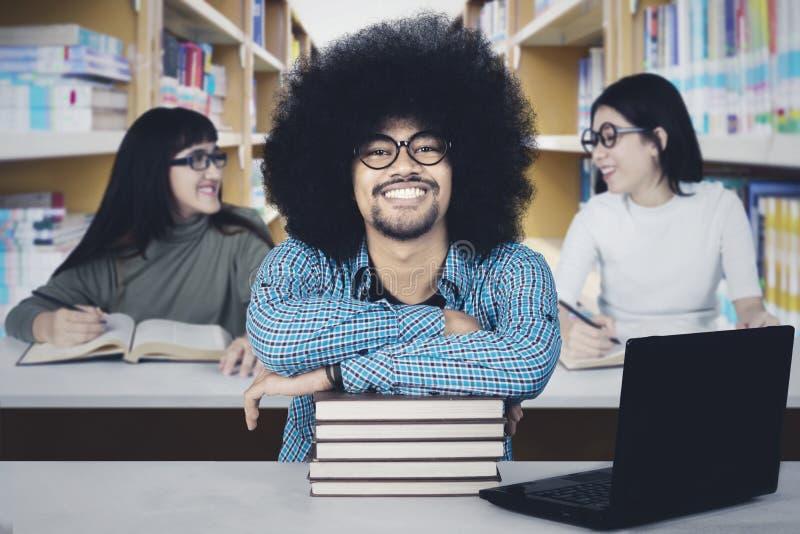 有他的朋友的蓬松卷发学生在图书馆里 免版税库存图片
