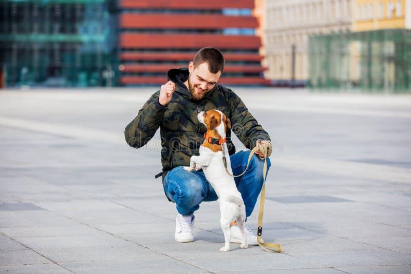 有他的狗的人,杰克罗素狗,在城市街道上 免版税库存照片