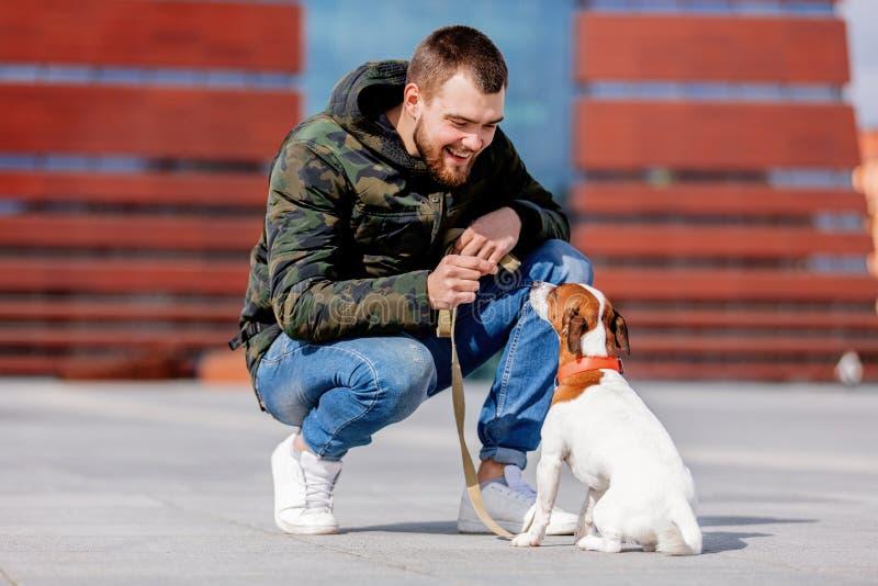 有他的狗的人,杰克罗素狗,在城市街道上 库存照片