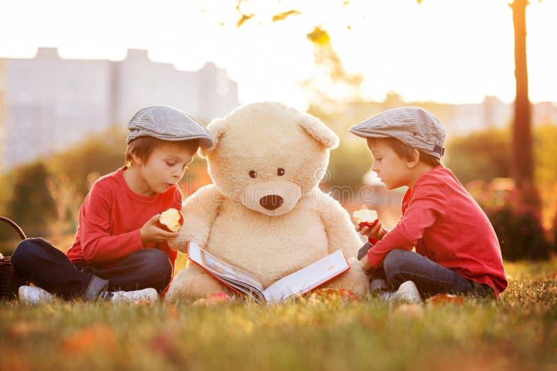 有他的玩具熊朋友的两个可爱的小男孩在公园 库存照片