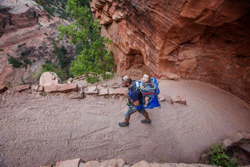 有他的男婴的一个人在锡安国立公园,犹他,美国迁徙 库存图片