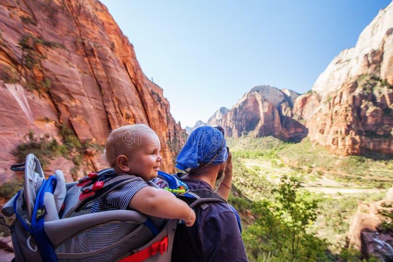 有他的男婴的一个人在锡安国立公园,犹他,美国迁徙 库存照片