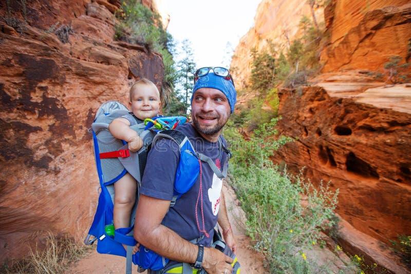 有他的男婴的一个人在锡安国立公园,犹他,美国迁徙 图库摄影