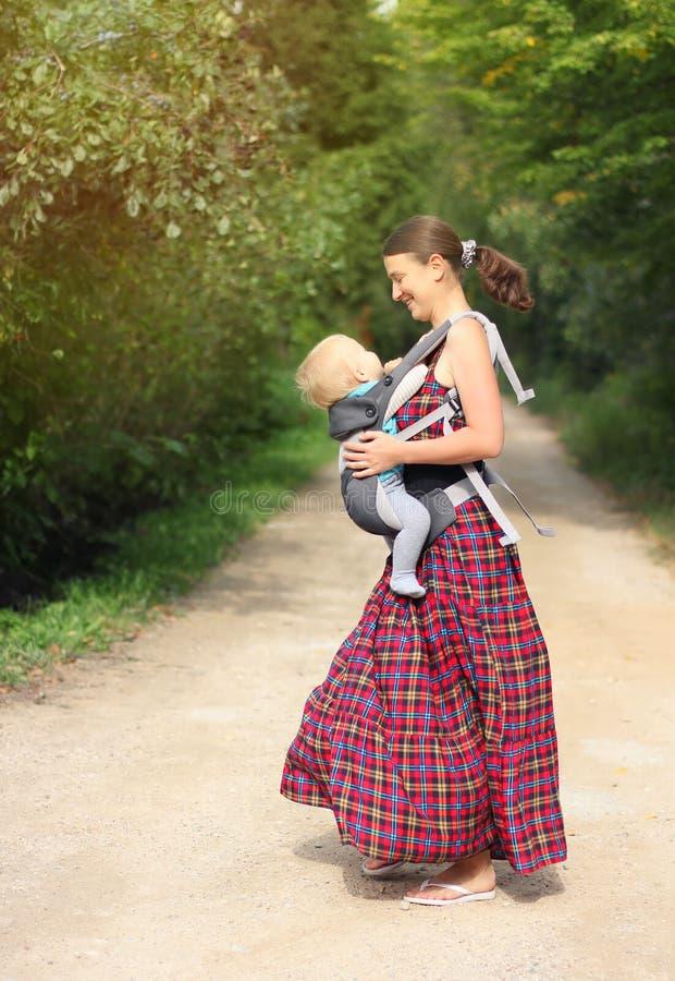 有他的男婴的母亲小型航空母舰的获得室外的乐趣 机会 免版税库存照片