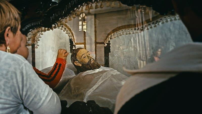 有他的看木耶稣雕象的母亲的年轻男孩地方教会在仪式期间星期天 库存照片