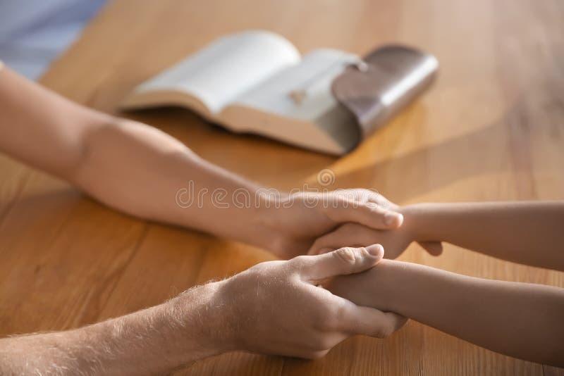 有他的祈祷在木桌,特写镜头上的孩子的父亲 免版税库存照片