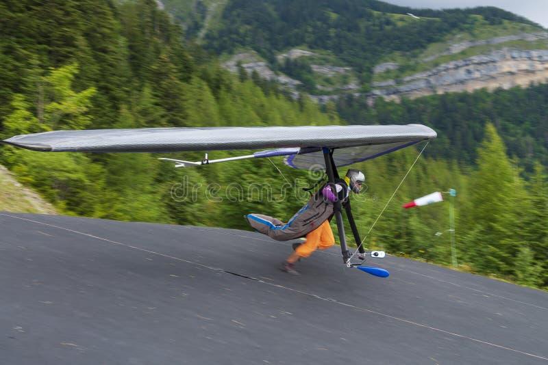 有他的翼的悬挂式滑翔机飞行员从小山快速地跑 免版税库存图片