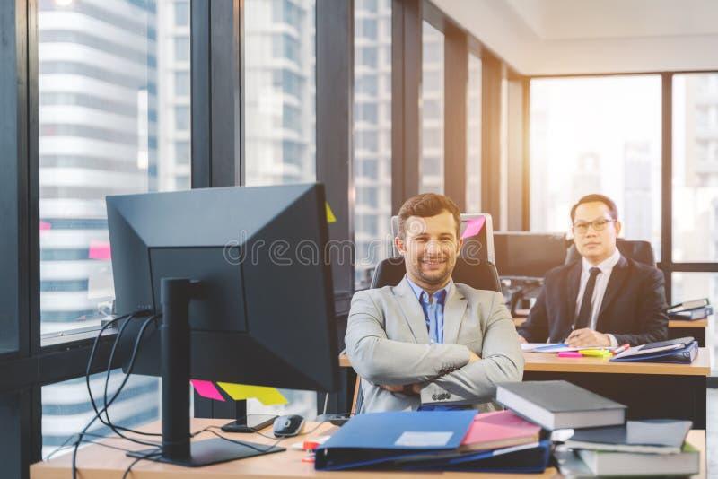 有他的职员的成功的商人在背景中在办公室 免版税库存图片