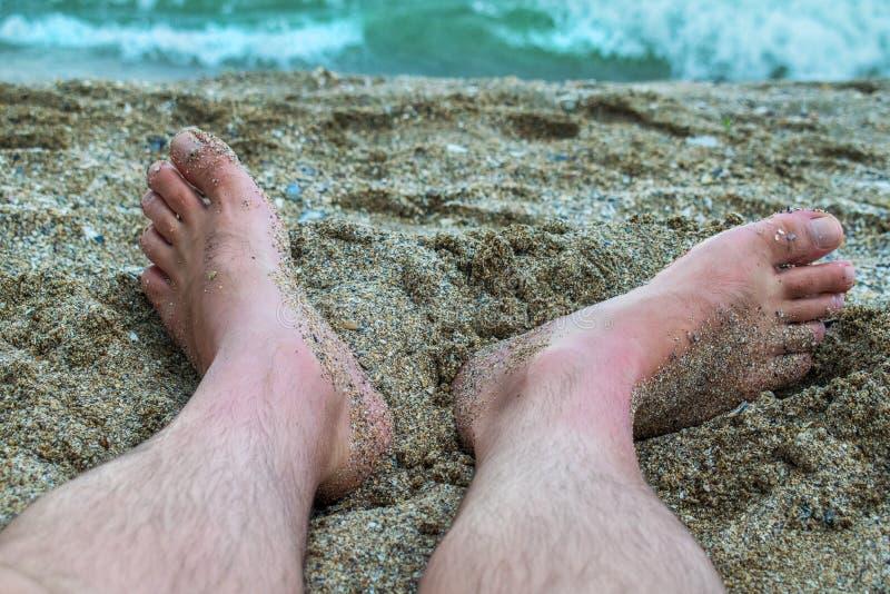 有他的脚的人在沙子,在海滨 假日开始了 库存图片