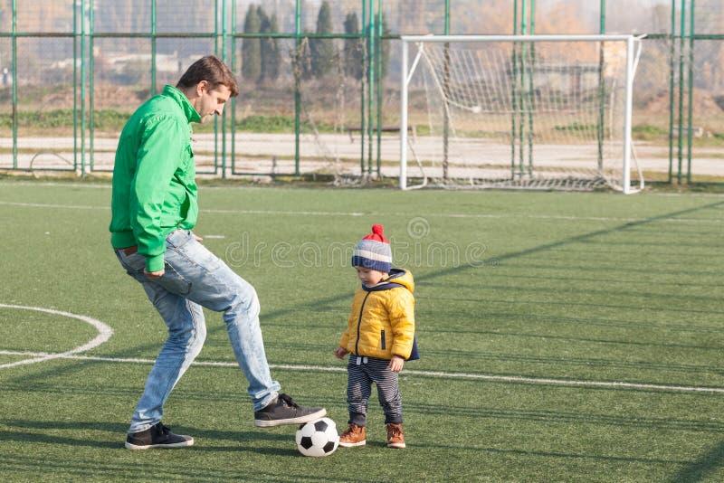 有他的踢橄榄球,足球的小儿子的年轻父亲在公园 免版税库存图片