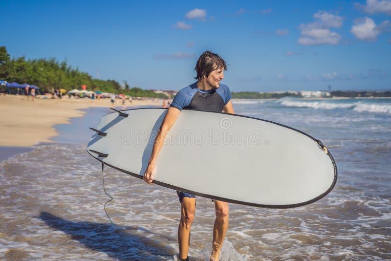 有他的运行到波浪的冲浪板的冲浪者 免版税库存照片