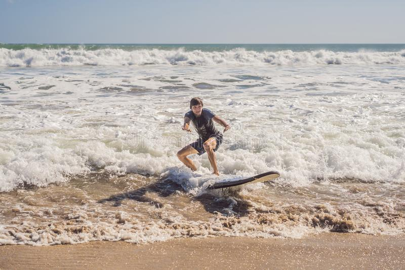 有他的运行到波浪的冲浪板的冲浪者 库存图片