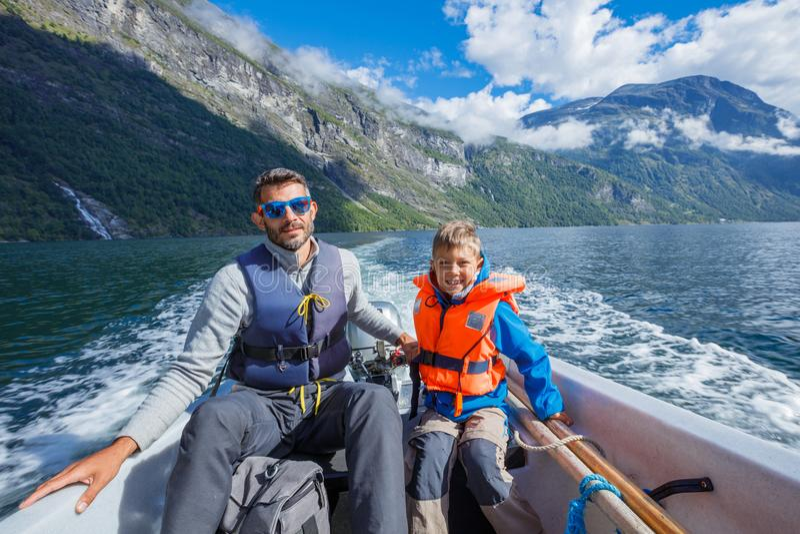 有他的驾驶汽艇,挪威的父亲的愉快的男孩 他们享受片刻 免版税库存照片