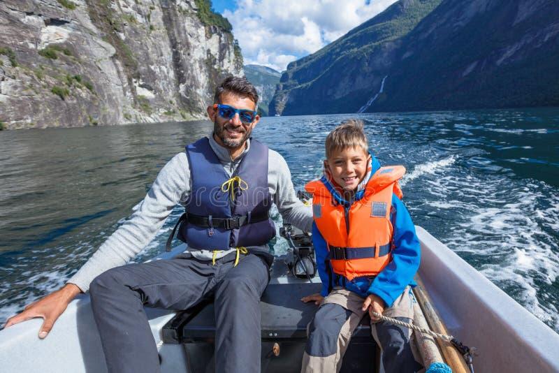 有他的驾驶汽艇,挪威的父亲的愉快的男孩 他们享受片刻 库存图片