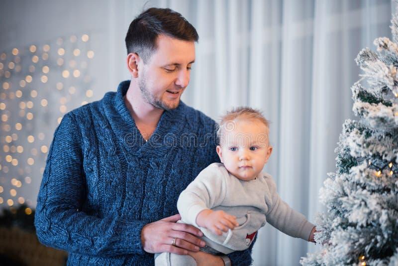有他逗人喜爱的一岁的儿子身分的愉快的父亲在圣诞树附近 免版税图库摄影