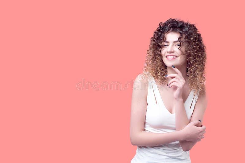 有令人惊讶的卷毛的愉快的微笑的少妇 库存照片