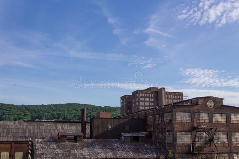 有以远现代商业大厦和树木丛生的山坡的遗弃工业仓库 库存照片