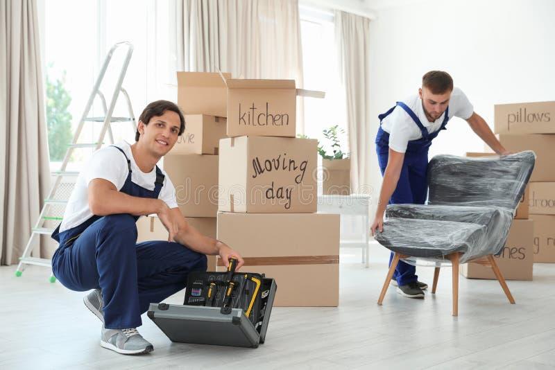 有仪器和扶手椅子的公搬家工人 库存图片