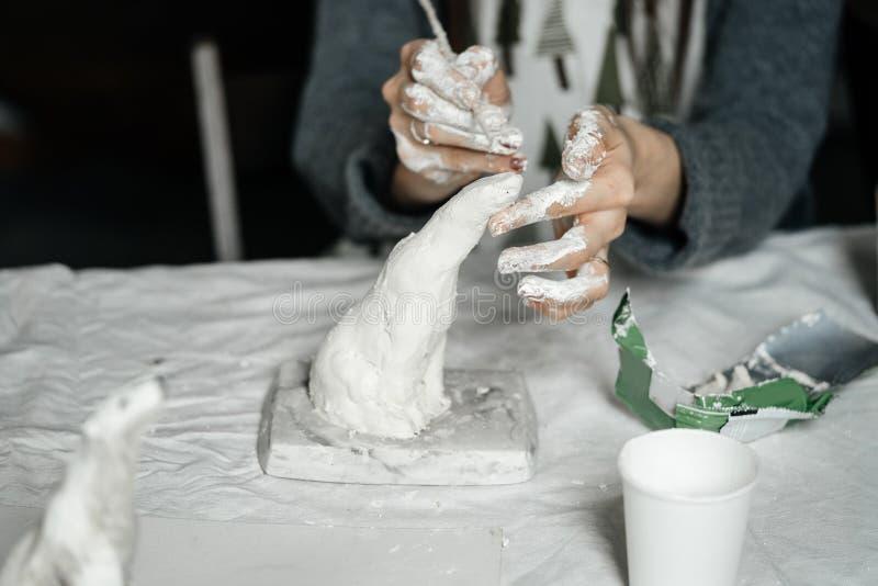 有仪器的女性手温文地塑造一个小膏药雕塑 库存照片