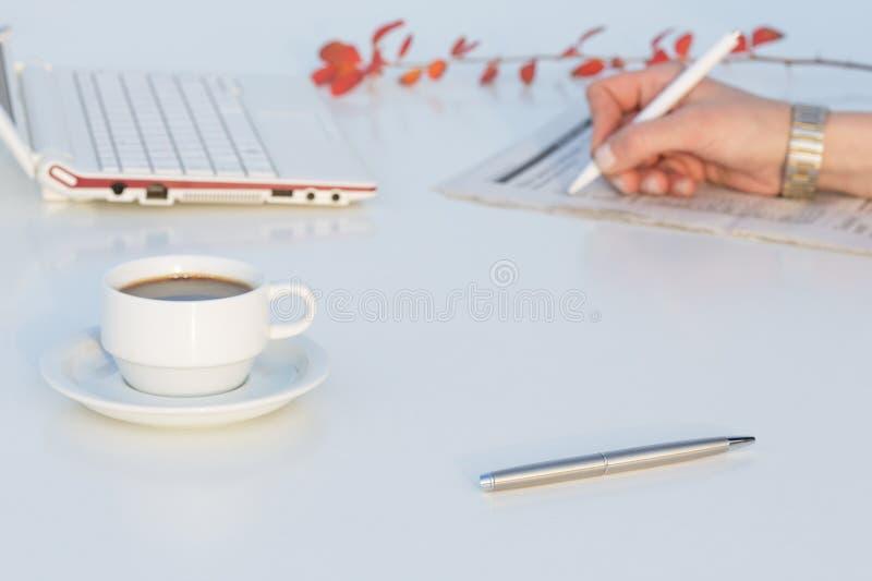 有企业项目和红色花的白色运转的书桌 库存图片