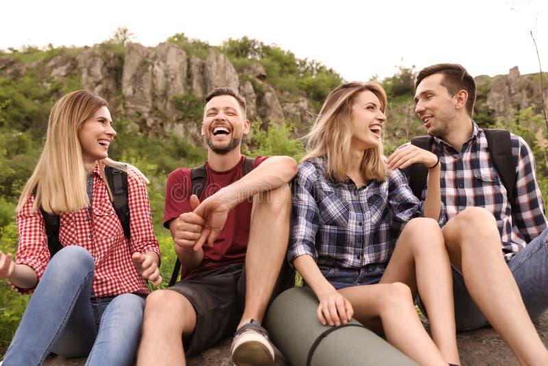 有休息在原野的背包的青年人 库存照片