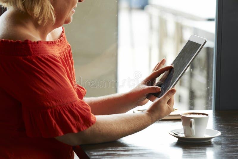 有休息在咖啡馆的片剂计算机的妇女 库存图片