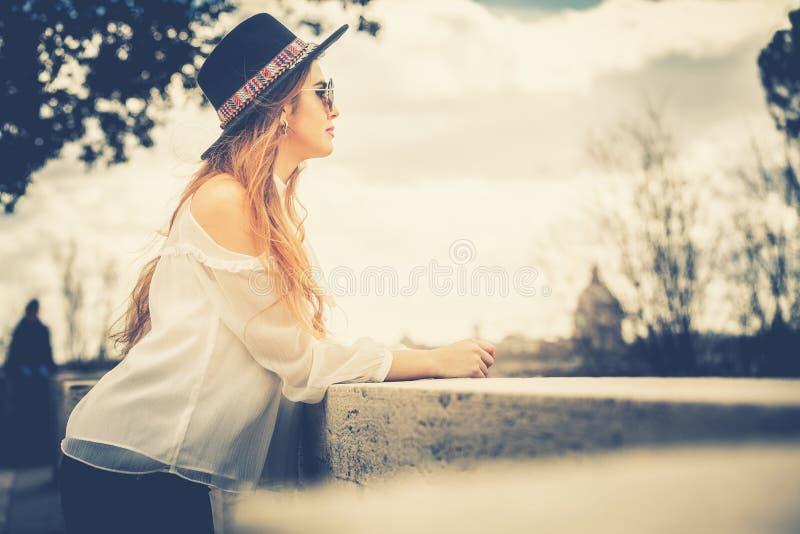 有休息在城市的帽子和太阳镜的少妇 免版税库存图片