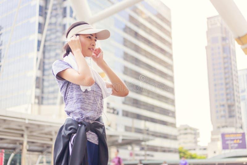 有休息在锻炼体育以后的白色毛巾的美丽的年轻亚裔妇女行使户外 库存照片