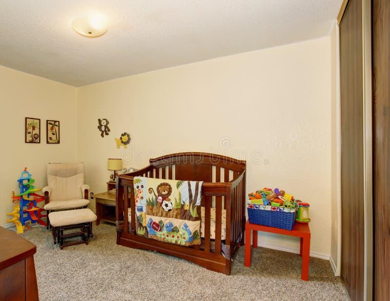 有优秀木小儿床的完善的婴孩室 免版税图库摄影