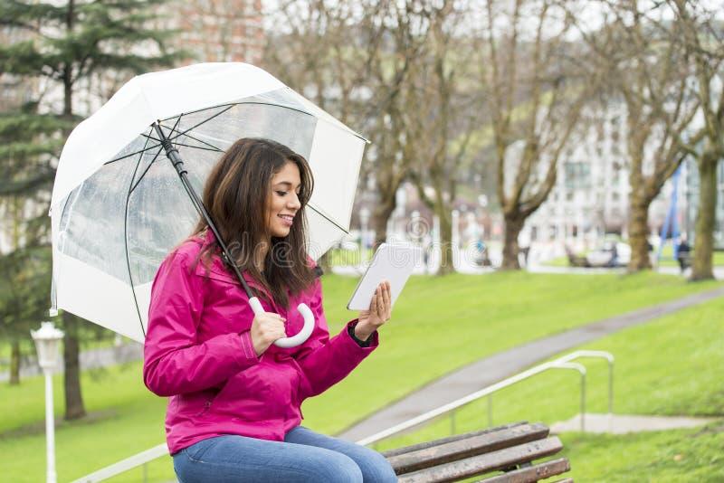 有伞和片剂计算机的幸福妇女在公园 库存照片