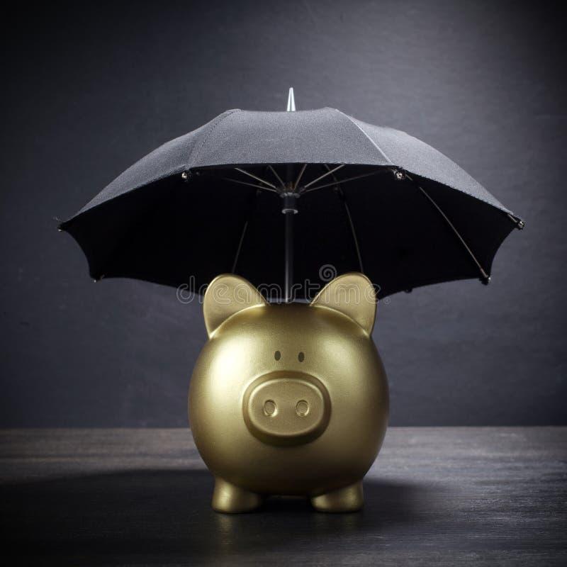 有伞概念的金存钱罐财务保险、保护、安全投资或者银行业务的 库存照片
