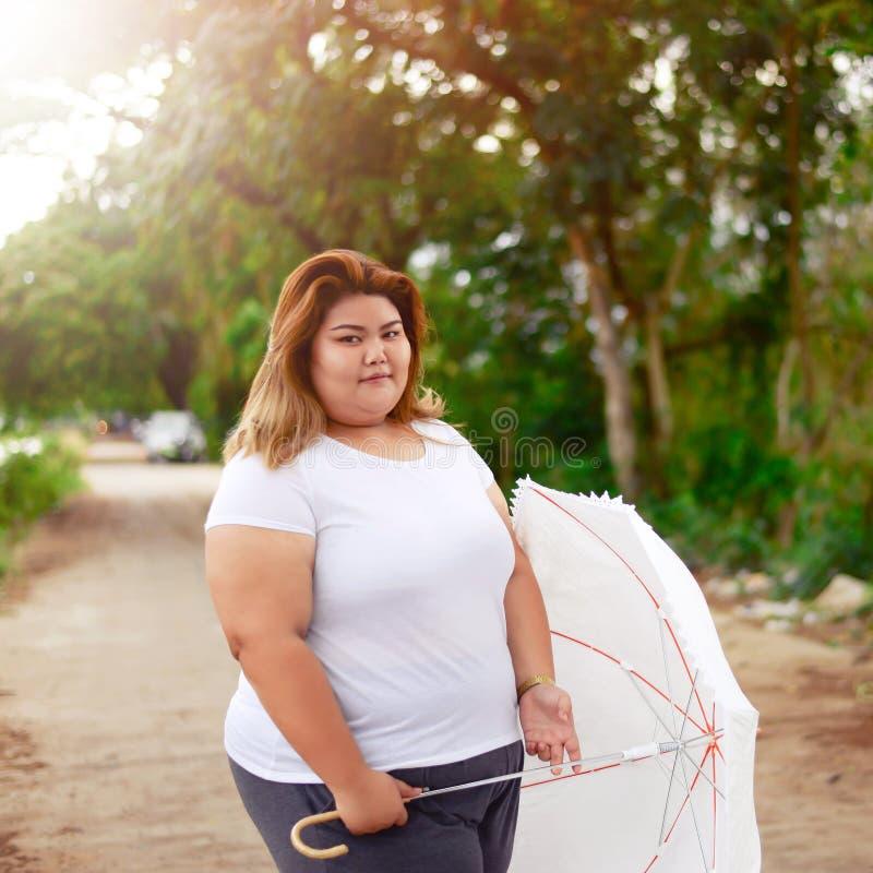 有伞的亚裔美丽的肥胖妇女在庭院里 免版税图库摄影
