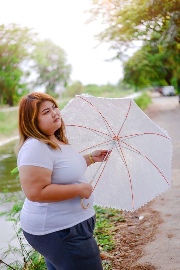 有伞的亚裔美丽的肥胖妇女在庭院里 免版税库存照片