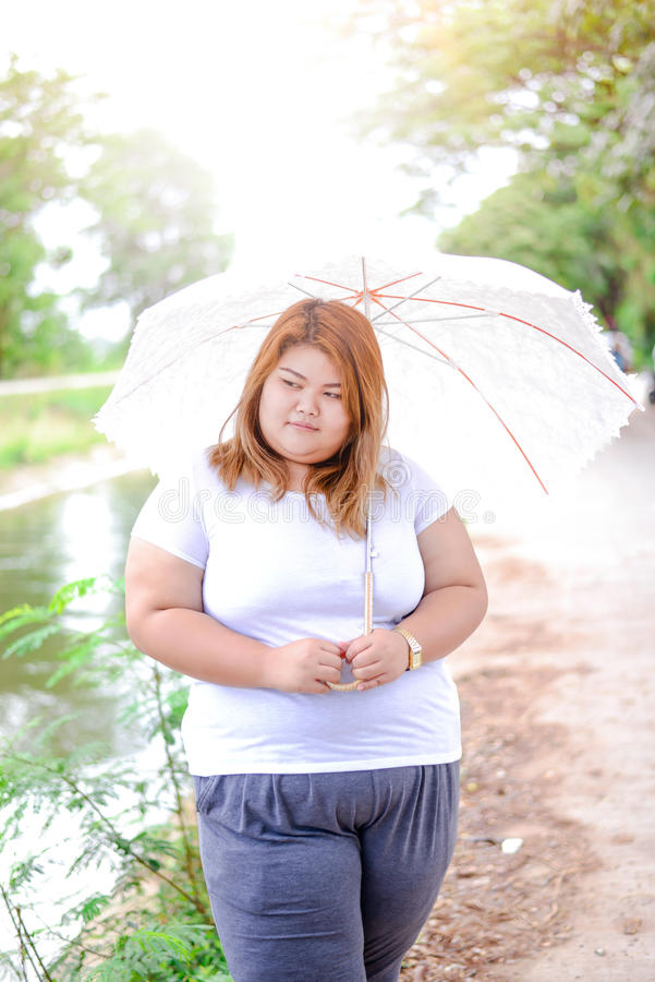 有伞的亚裔美丽的肥胖妇女在庭院里 库存图片