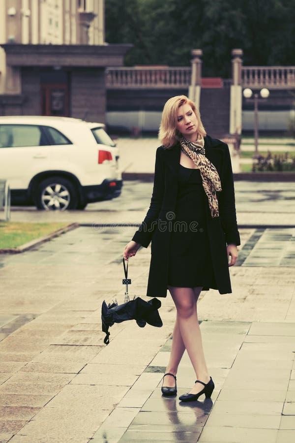 有伞的哀伤的年轻时尚妇女在城市街道上 免版税库存照片