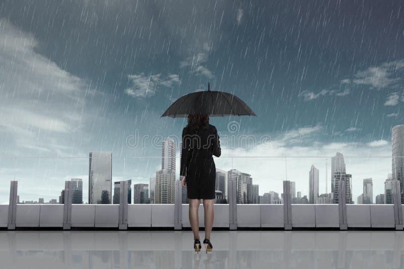 有伞的女商人在雨中 免版税库存照片