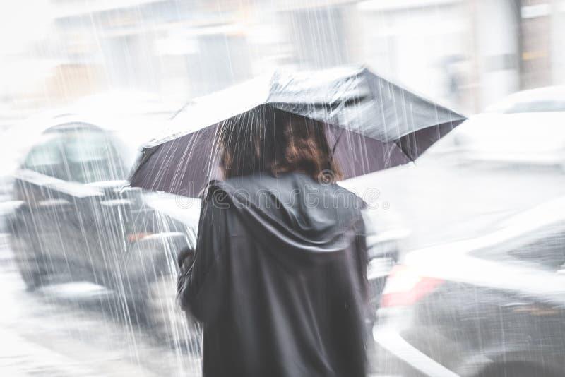 有伞的女孩在街道上在雨,迷离中 图库摄影