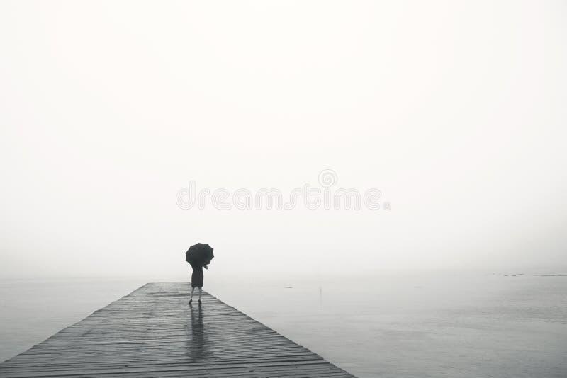 有伞的妇女在海前面平安地冥想 免版税图库摄影