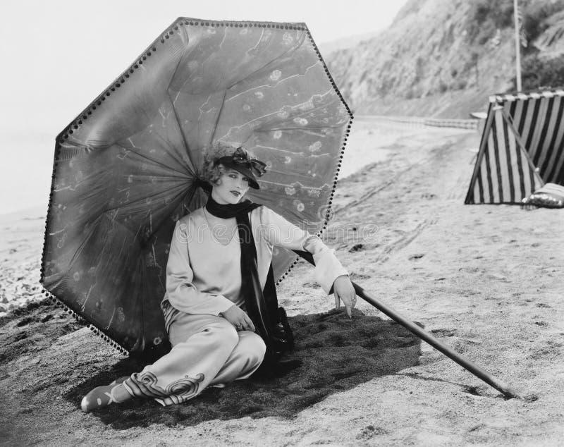 有伞的妇女在海滩(所有人被描述不更长生存,并且庄园不存在 供应商保单那里wil 免版税库存照片