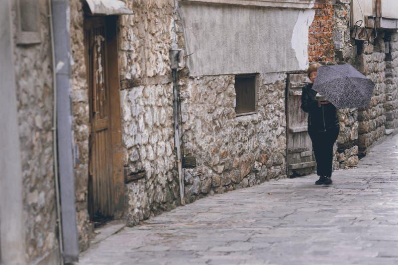 有伞的妇女在街道上在奥赫里德 免版税图库摄影