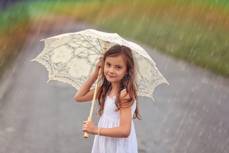 有伞的快乐的女孩在雨中 库存图片