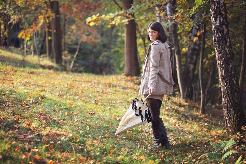 有伞的美丽的妇女在木头 免版税库存照片