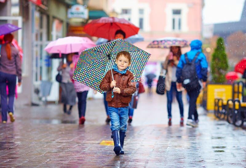 有伞的逗人喜爱的男孩走在拥挤城市街道上的 免版税图库摄影