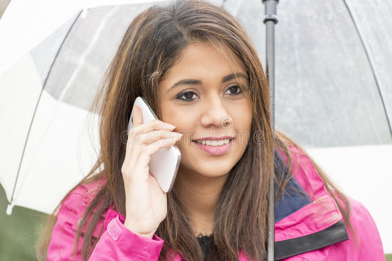 有伞的Cheerfull妇女谈话由手机 免版税库存图片