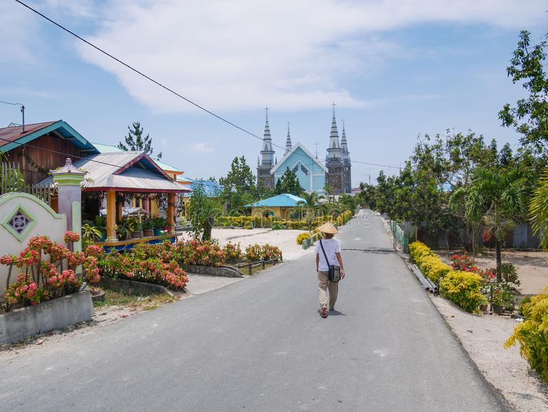 有传统帽子的妇女走在Ngurbloat街道,有一个巨大的基督徒gotic样式的一个微小的五颜六色的用花装饰的村庄的 免版税库存照片