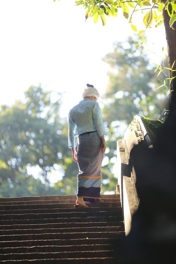 有传统泰国礼服的走在有树和日出的泰国寺庙的泰国年轻女人画象  免版税库存图片