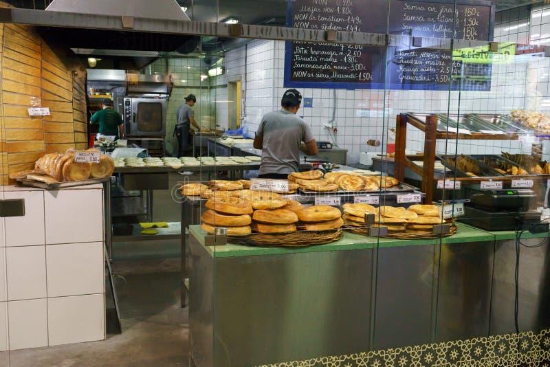 有传统火炉的东方面包店和新近地被烘烤的面包待售 库存照片