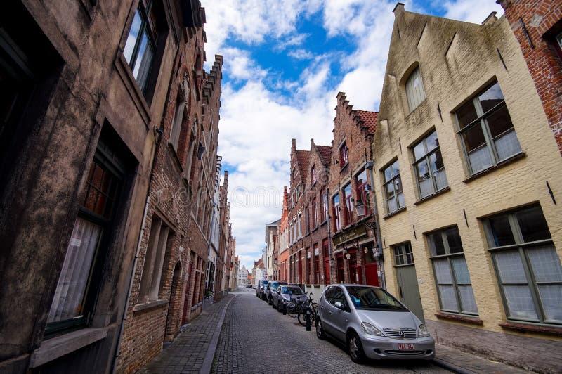 有传统砖房子的典型的老狭窄的被铺的街道在布鲁日 库存图片